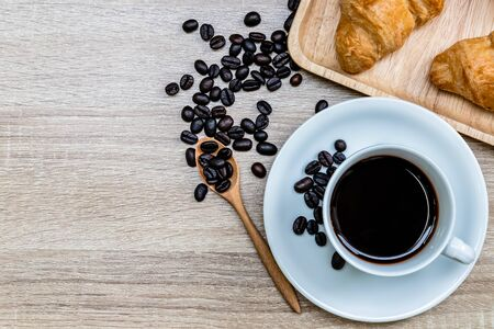 Coffee in white cup with coffee bean and croissants on wooden retro background, Breakfast concept Banco de Imagens