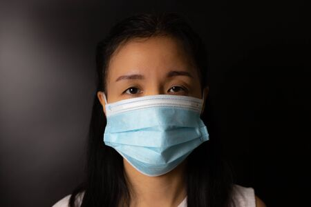 Woman wearing protection face mask against coronavirus or COVID-19 in darken tone. Banner with copyspace for medical concept