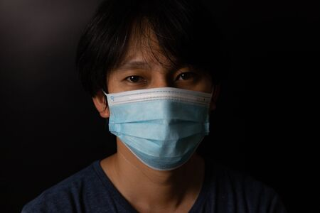 Man wearing protection face mask against coronavirus or COVID-19 in darken tone. Banner with copyspace for medical concept