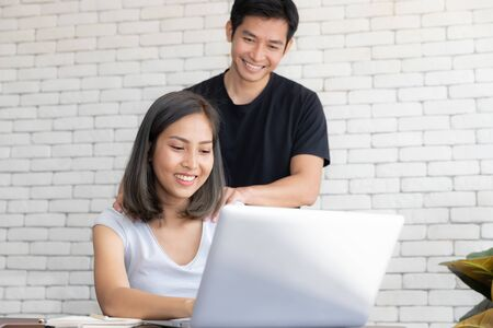 Portrait of young smiling couple working with laptop at home, A man massage shoulder of a girl for relaxing