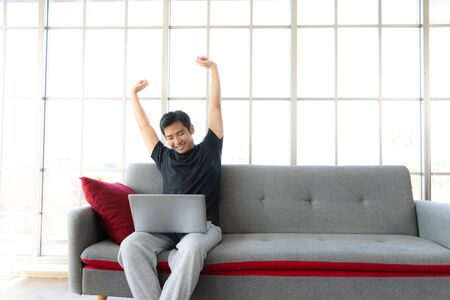 Asia man stretch oneself lazily while working with laptop, work from home concept