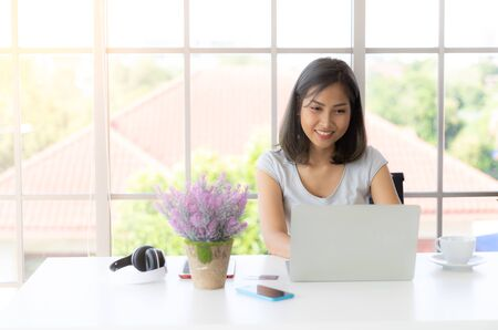 Portrait of smiling happy beautiful asian woman using laptop and typing on keyboard at home. work from home concept Zdjęcie Seryjne