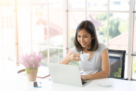 Portrait of smiling happy beautiful asian woman using technology of laptop computer while sitting, drinking coffee and typing on keyboard at home. Work at home concept 版權商用圖片