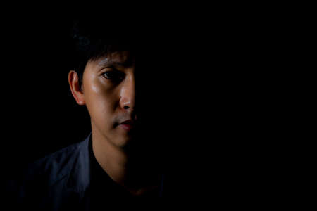Close up portrait of a man on black background with half face in shadow and copyspace