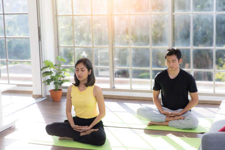 Couple of Asian boy and Asian young girl practicing yoga on mats in living room at home