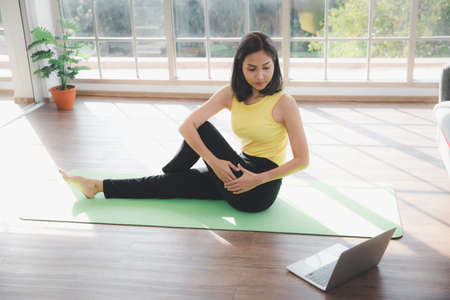 Asian young beautiful  woman practicing Yoga on mat and watching online tutorials on laptop in living room, Indoor sports activity