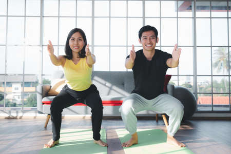 Couple of Asian boy and Asian young girl practicing yoga on mats in living room at home, Healthy indoor sports activity