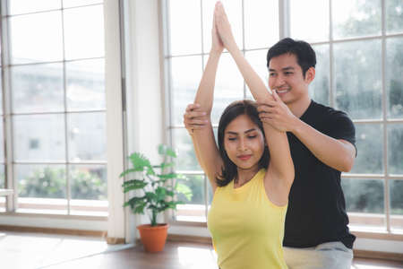 Asian young beautiful  woman practicing Yoga by stretching arm with a man trainer in living room at home, healthy Indoor sports activity 免版税图像