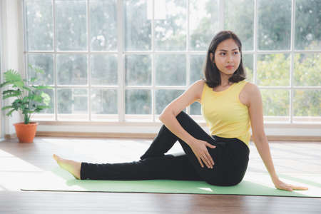 Asian young beautiful  woman practicing Yoga and exercising on mat at home, Indoor sports activity