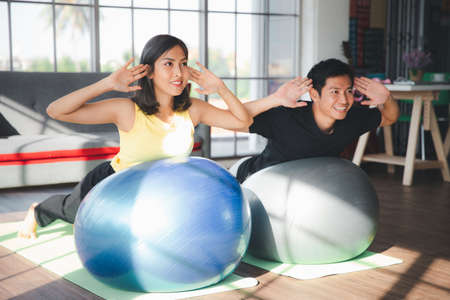 Couple of Asian boy and Asian young girl practicing yoga with exercise balls in living room at home, Healthy indoor sports activity