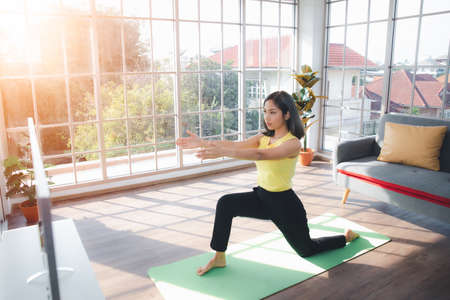 Asian young beautiful  woman practicing Yoga and exercising on mat in living room at home, healthy Indoor sports activity 免版税图像