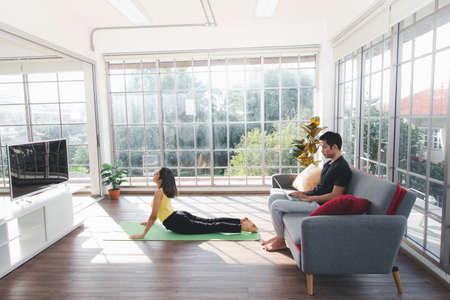Woman doing Yoga and Man using laptop in living room at home