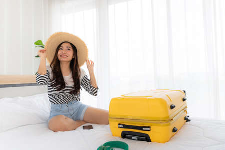 Young pretty asian woman dreaming and planning with yellow suitcase about holiday vacation and trip in bed room, travelling concept