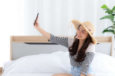 Portrait of cute girl having video call in bedroom with lover holding smart phone in hand shooting selfie on front camera enjoying  weekend vacation 免版税图像