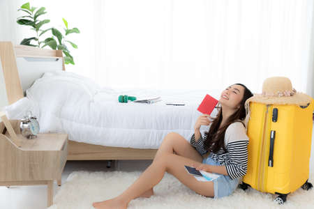 Happy young woman smiling and keep eye close while  lean to yellow baggage and sitting on floor at bedroom, summer or travelling concept 免版税图像