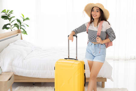 Beautiful young woman wearing short pants and standing with luggage bag and carrying backpack in bedroom for travelling and summer concept 免版税图像