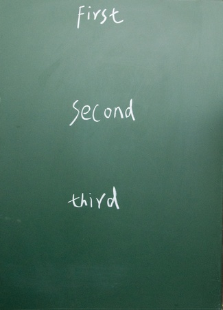 first second third title written with chalk on blackboard