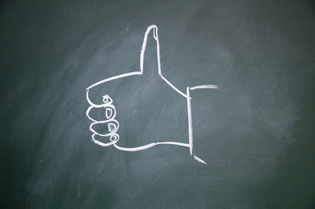 commend: Thumb drawn with chalk on blackboard Stock Photo