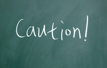 caution title written with chalk on blackboard photo
