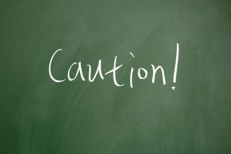 caution title written with chalk on blackboard Stock Photo - 12649225