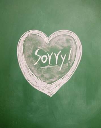 apology: sorry title and heart sign drawn with chalk on blackboard