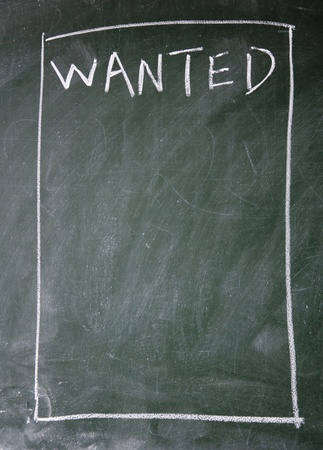 wanted title written with chalk on blackboard photo
