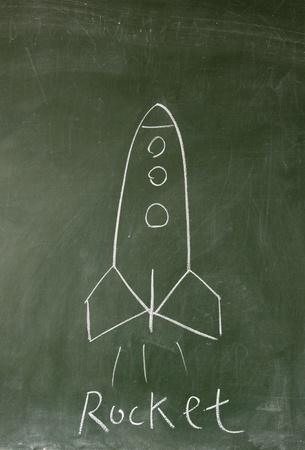 rocket drawn with chalk on blackboard photo