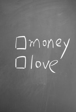 money or love choice written with chalk on blackboard photo