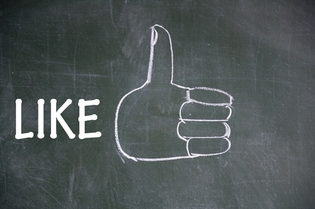 commend: thumb up gesture drawn with chalk on blackboard