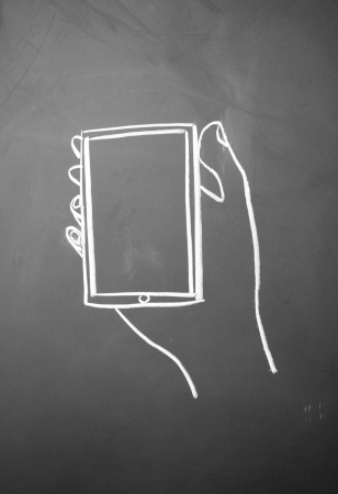 A person holding a cell phone symbol drawn with chalk on blackboard photo