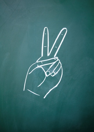 Victory sign drawn with chalk on blackboard 版權商用圖片 - 14922465
