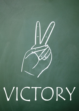 Victory sign drawn with chalk on blackboard photo