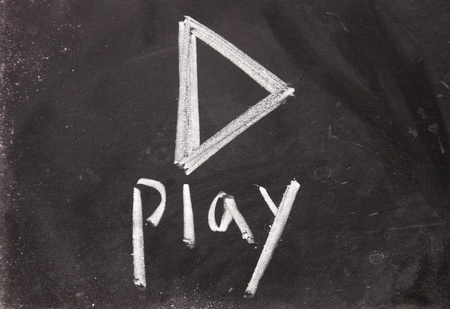 pause button: play sign drawn with chalk on blackboard