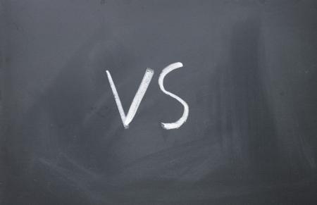 vs sign written with chalk on blackboard Standard-Bild
