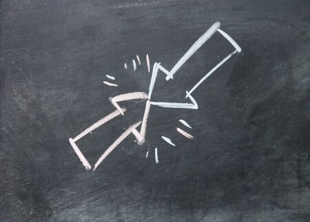 counterpoise: Arrow symbol collision drawn with chalk on blackboard