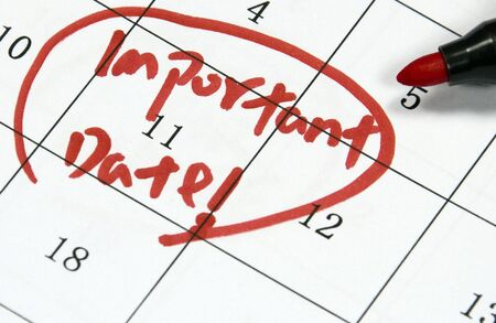 important date sign written with pen on paper photo