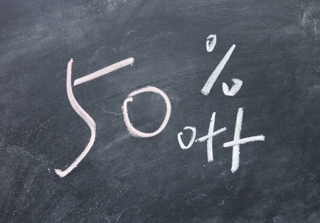 clearance: 50  discount sign written with chalk on blackboard Stock Photo
