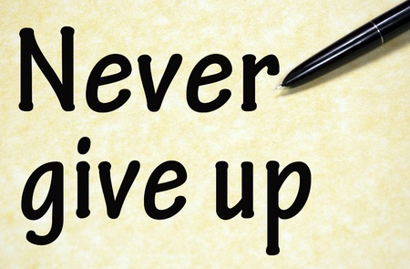 never give up title written with pen on paper photo