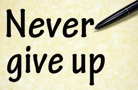 nunca: nunca te rindas t�tulo escrito con la pluma en el papel Foto de archivo