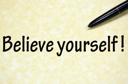 believe in yourself title written with pen on paper photo