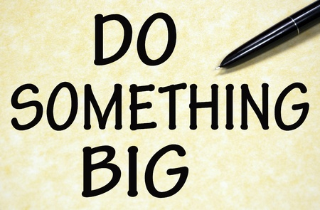 do something big title written with pen on paper photo