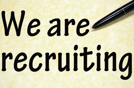 recruiting: we are recruiting title written with pen on paper