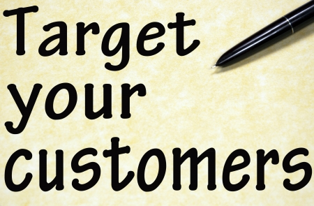 target your customers title written with pen on paper photo