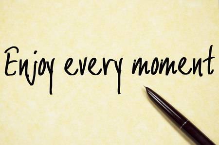 moment: enjoy every moment text write on paper