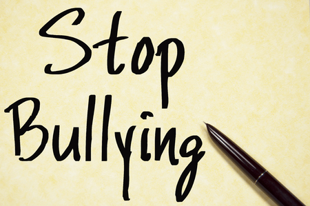 intimidation: stop bullying text write on paper