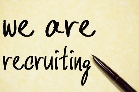 recruiting: we are recruiting text write on paper