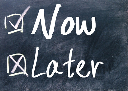 later: now and later choice on blackboard Stock Photo