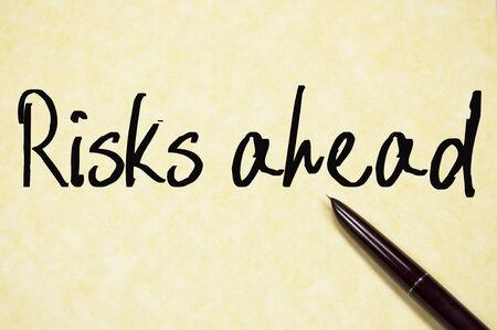 risks ahead: riesgos por delante texto de escritura en papel