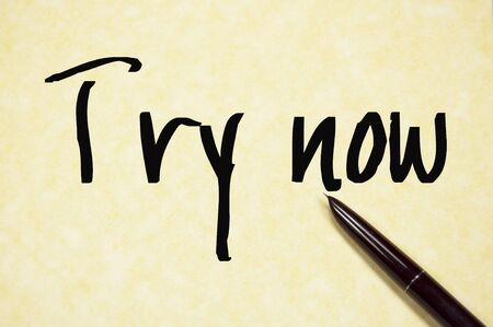to try: try now sign on paper Stock Photo