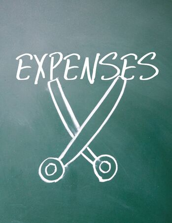expenses: expenses cut sign on blackboard Stock Photo